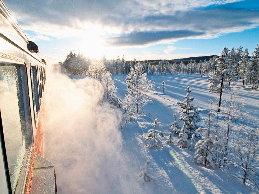 Tåg på Inlandsbanan, snö yr och solen skiner